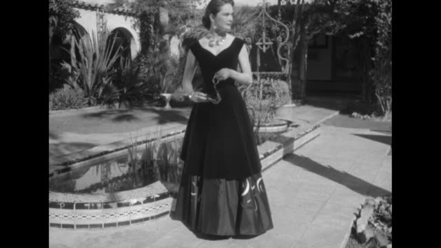 vs female model wearing a dark floorlength gown poses in spanishstyle courtyard of the royal palms inn / she then stands next to large studded wooden... - courtyard stock videos and b-roll footage