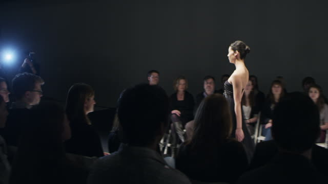 ms female model wearing gown walking alone on catwalk in front of crowd at fashion show  - fashion show点の映像素材/bロール