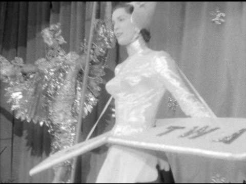 female model wearing 'twa' costume w/ wings on stage walking around grand ballroom in hotel astor during charity ball nyc - twa video stock e b–roll