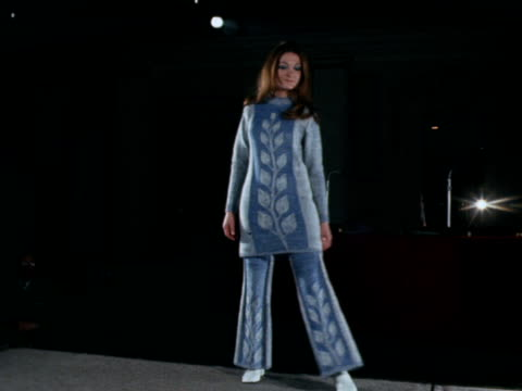 a female model wears a woollen top and trousers on the catwalk the model then takes off the trouser legs and the top becomes a mini dress 1970 - trousers stock videos & royalty-free footage