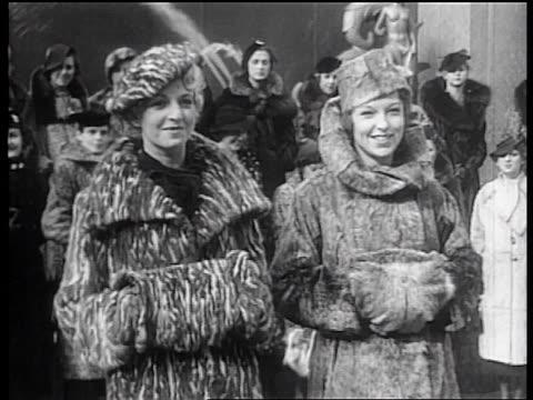 b/w 1936 portrait 2 female models posing with fur coats + matching hats at rockefeller center, nyc - 毛皮のコート点の映像素材/bロール