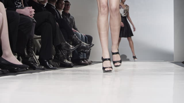 MS LA Female models walking down catwalk during fashion show model rolls ankle over in the middle of the catwalk