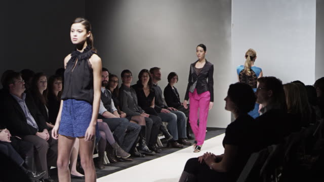 ms female models walking down catwalk during fashion show - model stock-videos und b-roll-filmmaterial