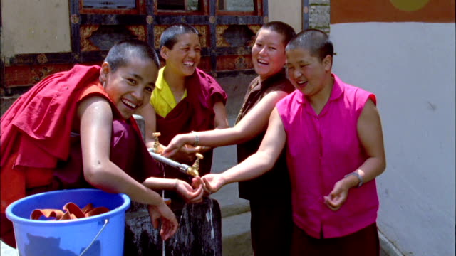female monks laugh and splash water while washing available in hd. - bhutan stock videos & royalty-free footage