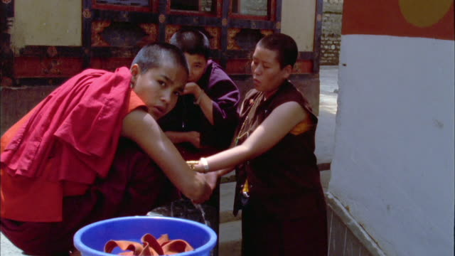 Female monks washing at tap Available in HD.