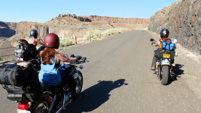 MS ZI Female motorcyclists on road trip through desert canyon rear view
