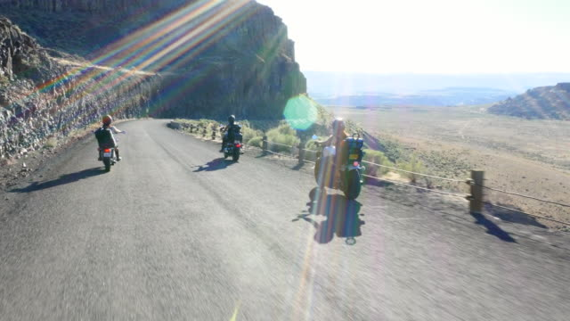 vidéos et rushes de ws pan zi female motorcyclists on road trip through desert canyon - visage caché