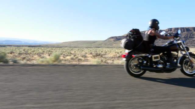 MS Female motorcyclists riding on desert canyon road on summer evening