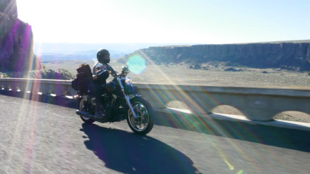 WS Female motorcyclists riding on desert canyon road with arm raised on summer evening