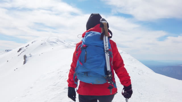 female mountain alpine climber is moving up with her team in the high altitude mountain peak in winter - winter sport stock videos & royalty-free footage