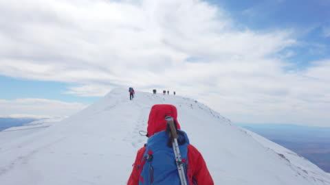 vídeos y material grabado en eventos de stock de mujer escaladora alpina de montaña se está moviendo hacia arriba con su equipo en el pico de la montaña de gran altitud en invierno - moverse hacia arriba