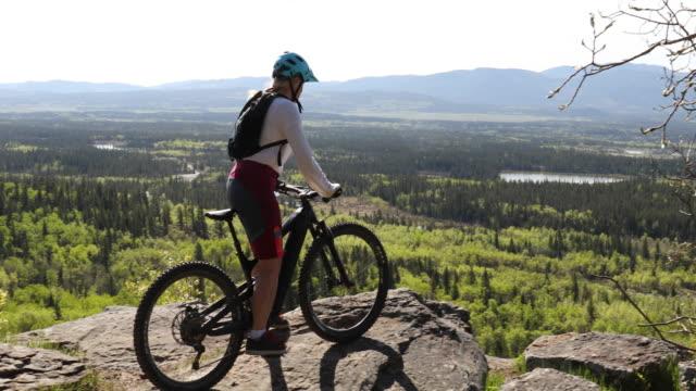 stockvideo's en b-roll-footage met de vrouwelijke mountainbiker komt op klipboven boven aspenbomen aan - fietshelm