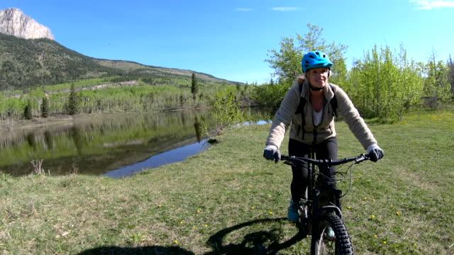 female mountain bike rider traverses meadow past aspen trees - mountain biking stock videos & royalty-free footage