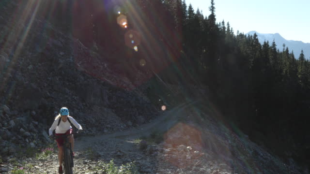 female mountain biker ascends rocky track - bicycle trail outdoor sports stock videos & royalty-free footage
