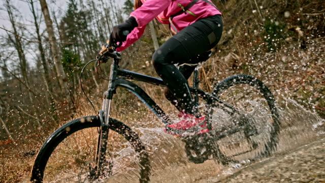slo mo weibliche mountainbiker überquerung eines baches auf ihrem fahrrad - extremsport stock-videos und b-roll-filmmaterial