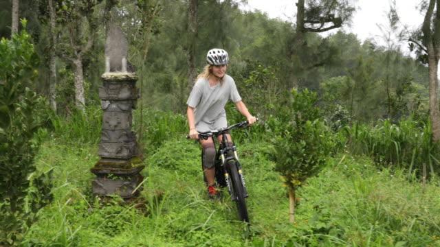 vidéos et rushes de vététiste femelle descend le chemin de la jungle - faire du vélo tout terrain