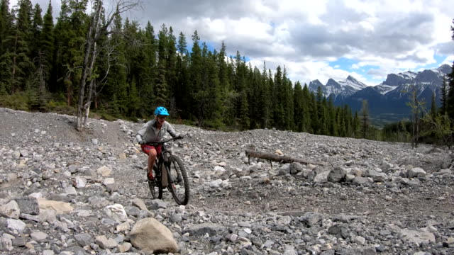 female mountain biker follows mountain path though boulder field - mountain bike video stock e b–roll