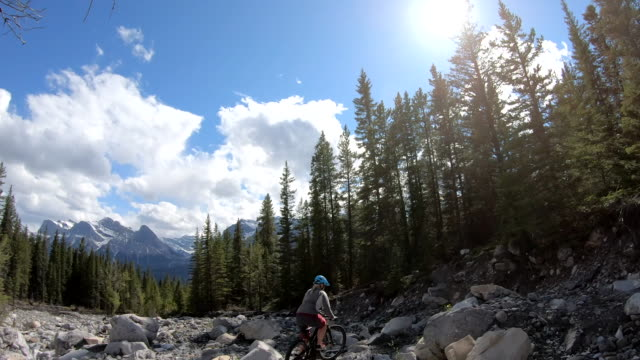 vídeos de stock e filmes b-roll de female mountain biker follows mountain path though boulder field - só uma mulher madura