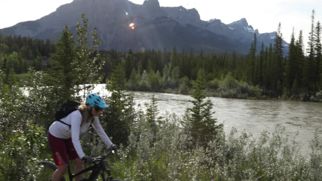 vídeos de stock e filmes b-roll de female mountain biker follows path near river's edge - só uma mulher madura