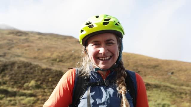 female mountain biker in the scottish highlands smiling to camera - mountain biking stock videos & royalty-free footage