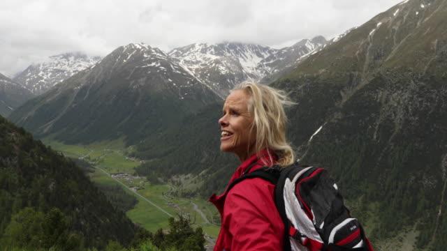 female mountain biker leaves hut doorway - rucksack stock-videos und b-roll-filmmaterial