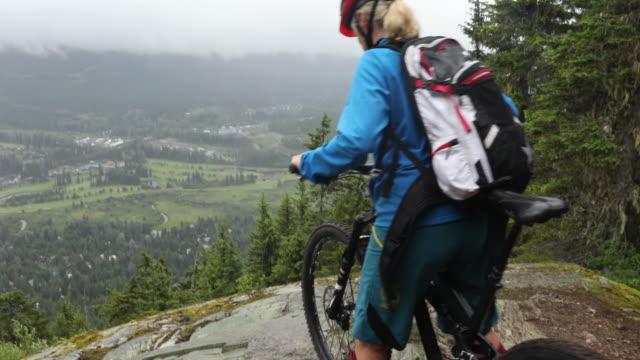 Kvinnliga mountain biker look ut i dimma över byn, dalen