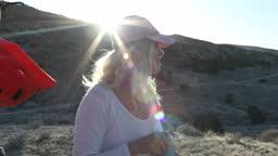 Female mountain biker looks out across desert landscape, after ride