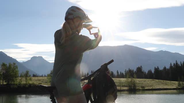 vídeos y material grabado en eventos de stock de mujer ciclista de montaña hace una pausa en el borde del lago de montaña - menos de diez segundos