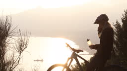 Female mountain biker pauses on forested ridge