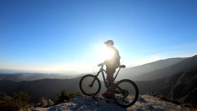 vídeos de stock e filmes b-roll de female mountain biker pauses on mountain summit - ficar de pé