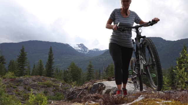 Kvinnliga mountainbikecyklist skjuter cykel över karga västkusten Lanscape