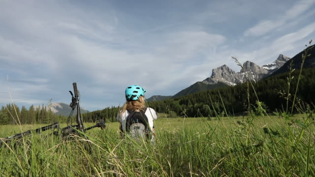 vídeos de stock e filmes b-roll de female mountain biker relaxes in mountain meadow - só uma mulher madura
