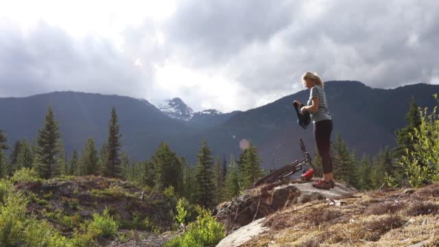 Kvinnliga mountainbike-åkaren tar bort tröja, robust västkusten Lanscape
