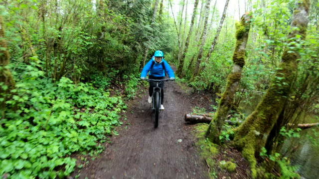 female mountain biker rides along forested path - mountain bike stock videos & royalty-free footage