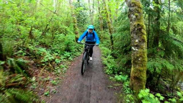 female mountain biker rides along forested path - sports track stock videos & royalty-free footage
