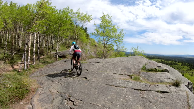 vídeos de stock e filmes b-roll de female mountain biker rides e-bike along rock slabs - árvore de folha caduca