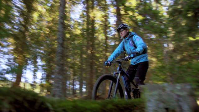 Female mountain biker riding through forest in sunshine