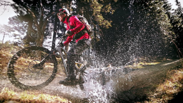 speed ramp female mountain biker riding through forest puddle - andare in mountain bike video stock e b–roll