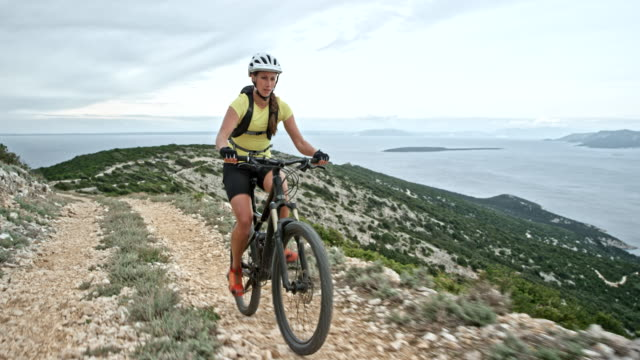 Female mountain biker riding up a mountain ridge on a rocky road overlooking the sea