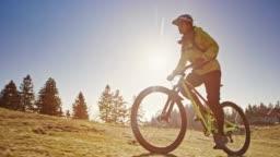 SLO MO TS Female mountain biker riding up the mountain meadow in sunshine