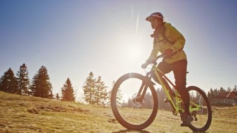 stockvideo's en b-roll-footage met slo mo ts vrouwelijke mountainbiker rijden op de weide van de berg in de zon - cycling