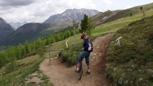 female mountain biker stops at trail fork, determines direction - stop single word stock videos & royalty-free footage