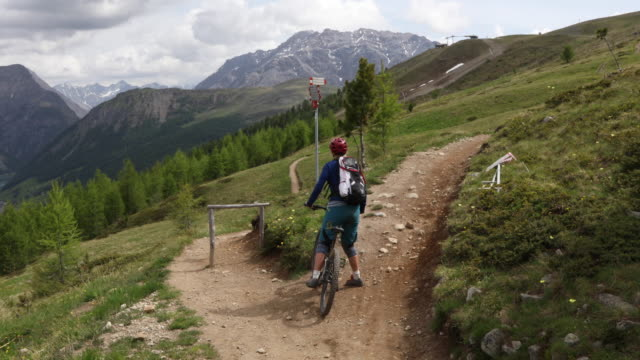 female mountain biker stops at trail fork, determines direction - entscheidung stock-videos und b-roll-filmmaterial