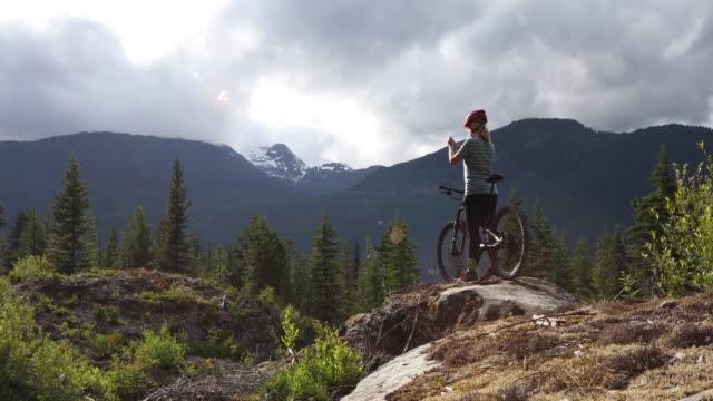 Kvinnliga mountainbike-åkaren tar smart telefon pic av robust västkusten landskap