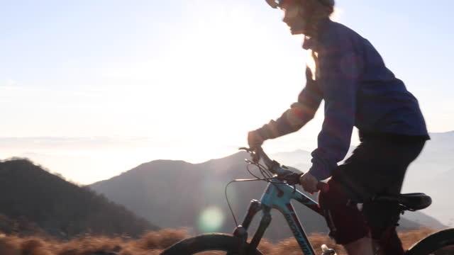 女性マウンテンバイカーは、山頂の近くで、高山のトレイルを横断します - サイクリングロード点の映像素材/bロール