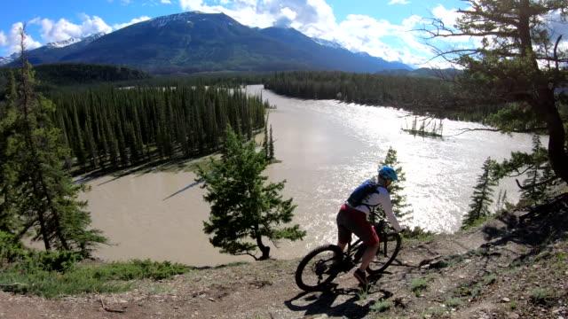 female mountain biker traverses hillside above roaring river - ジャスパー国立公園点の映像素材/bロール