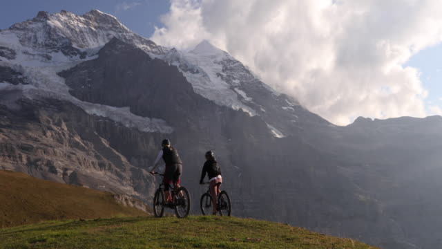 female mountain bikers traverse mountain meadow at sunrise - looking away stock videos & royalty-free footage