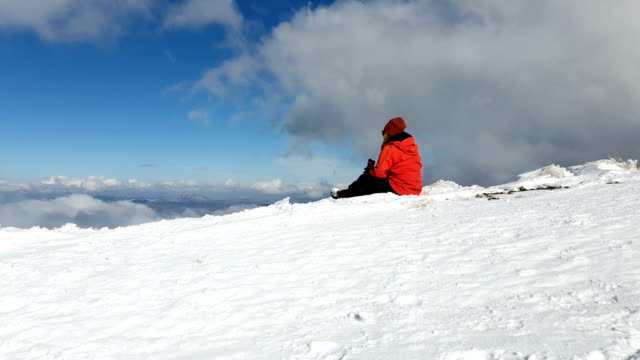 kvinnlig bergsbestigare dricka kaffe i toppen av hög höjd berget på vintern vid soluppgången - klätterutrustning bildbanksvideor och videomaterial från bakom kulisserna