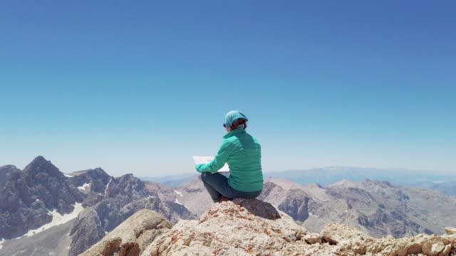 vidéos et rushes de l'alpiniste féminin regarde la carte dans le sommet d'une montagne - sports extrêmes