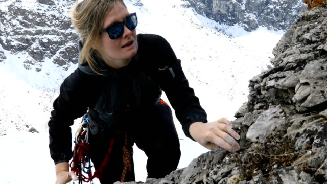 female mountaineer makes final moves up rugged cliff face to top of ledge. - snowcapped mountain stock videos & royalty-free footage